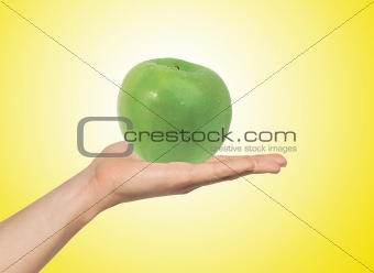green apple on the hand over yellow