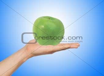 green apple on the hand over blue