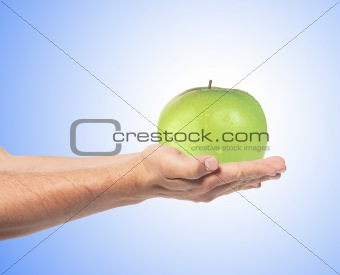 Green apple on man's hand over blue background