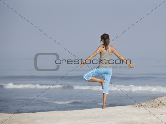 Beautiful young woman with arms open, relaxing on the beach