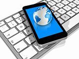 world globe on a mobile phone on a computer keyboard