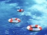Three lifebuoys, floating on waves