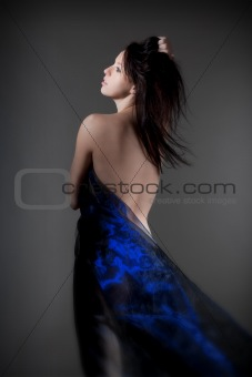 beautiful nude woman with dark hair in blue cloth - isolated on gray