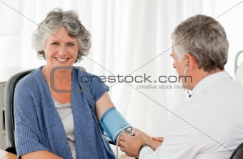 A senior doctor taking the blood pressure of his patient