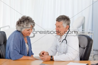 A senior doctor with his patient in his office