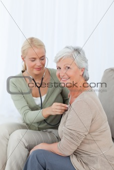 Nurse taking the heartbreat of her patient at home