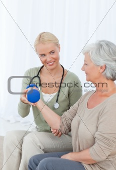 Beautiful nurse helping her patient to do exercises