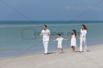 Mother, Father and Children Family Walking Holding Hands On Beac