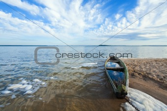 Old flooding boat on summer lake shore