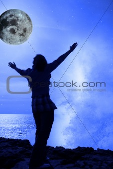 a woman with raised hands facing a wave and full moon on cliff e