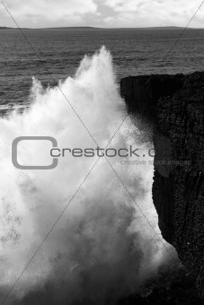 giant wave crashing on coastline cliffs
