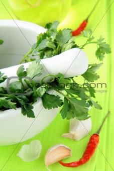 green parsley in a mortar with garlic and pepper
