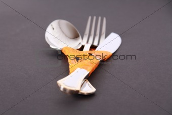 Fork, knife and spoon with orange ribbon