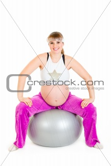 Smiling beautiful pregnant female doing exercises on fitness ball