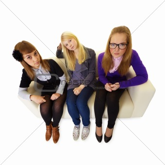 Three girlfriends are sitting on the couch