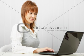 Attractive smiling happy girl with a laptop