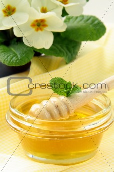 fresh golden honey in jar  with a wooden spoon