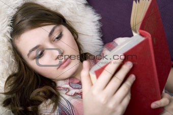 Beautiful girl reading book, closeup portrait