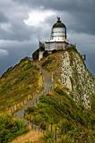 Nugget Point Light House and dark clouds in the sky
