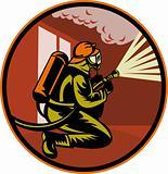 Fireman firefighter kneeling with fire hose