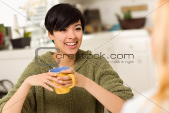 Multi-ethnic Young Attractive Woman Socializing with Friend in Her Kitchen.
