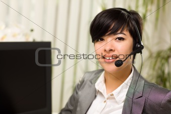 Attractive Young Woman Smiles Wearing Headset Near Her Computer Monitor.