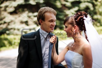 Beautiful couple newlywed, bride pulling her groom in by his neck