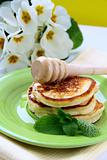 Traditional pancakes with honey and mint on a plate