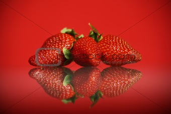 Three strawberries against red background