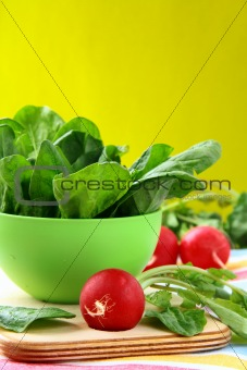 Fresh spinach in a green bowl on a cutting board