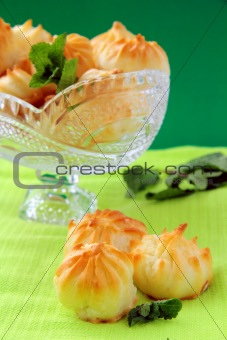 Cake profiteroles  in a crystal vase on a green background