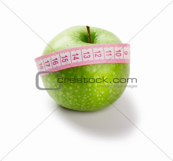 Green apple and measuring tape of the tailor isolated on white