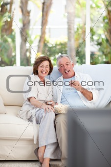 Seniors watching tv at home