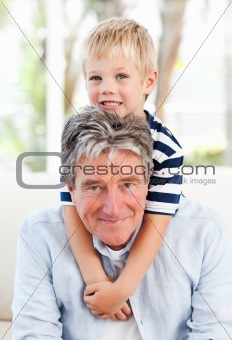 Little boy with his grandfather looking at the camera