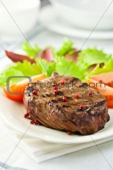 Grilled steak served with fresh vegetables