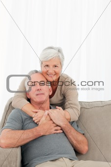 Lovers hugging while they are looking at the camera