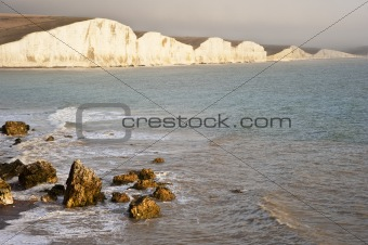 Beautiful landscape of rolling waves and white cliffs with rocks