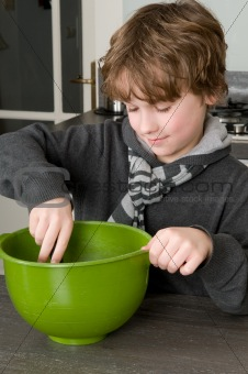 Boy making the dough for the cakes