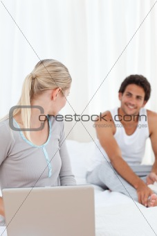 Woman talking with her boyfriend on the bed 