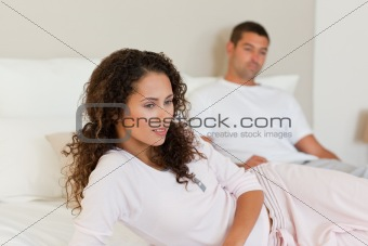 Thoughtful woman with her husband on the bed