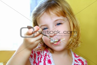 hungry little blond girl spoon eating ice cream