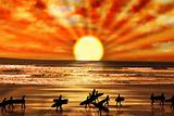 surfers walking on sunset beach