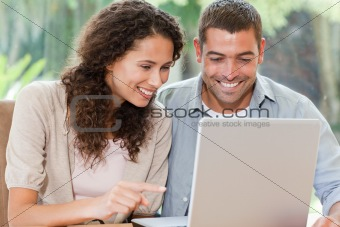 Lovers looking at their laptop at home