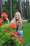 Pretty gardener woman with red flower bush and gardening tools