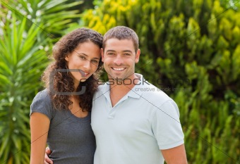 Happy couple hugging in the garden