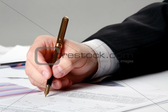 Male hand is writing in business document