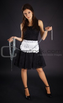 Young servant girl in black dress holding a chain