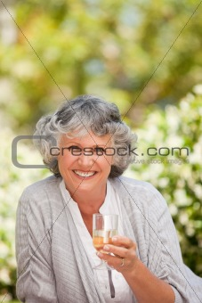 Smilimg woman with her drink of wine