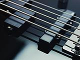detail of electric bass, pickups and cords