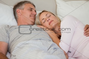 Beautiful couple sleeping on their bed